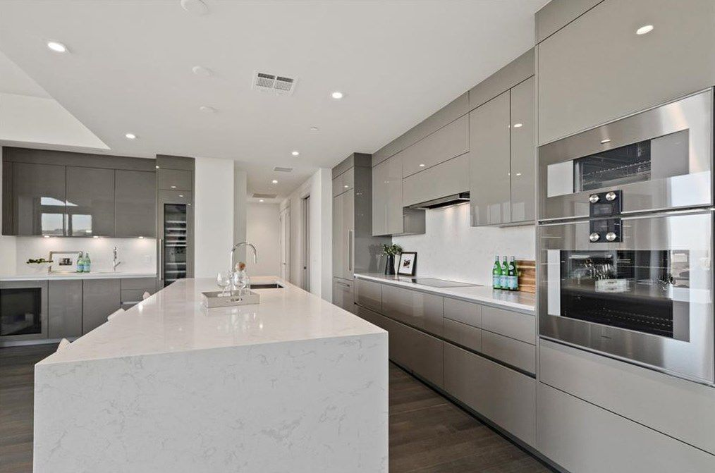 A white and gray modern kitchen with white countertops.