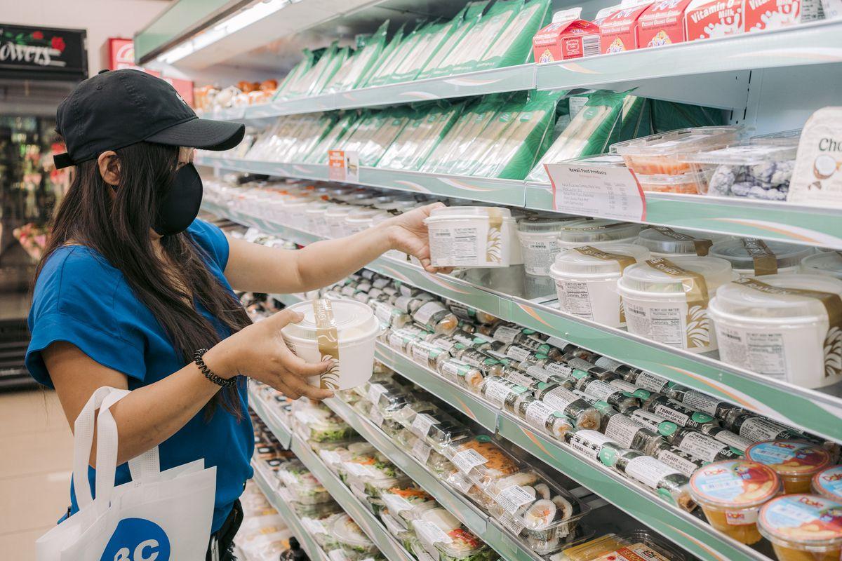 a woman picks up a bowl of ramen in a shopping aisle.