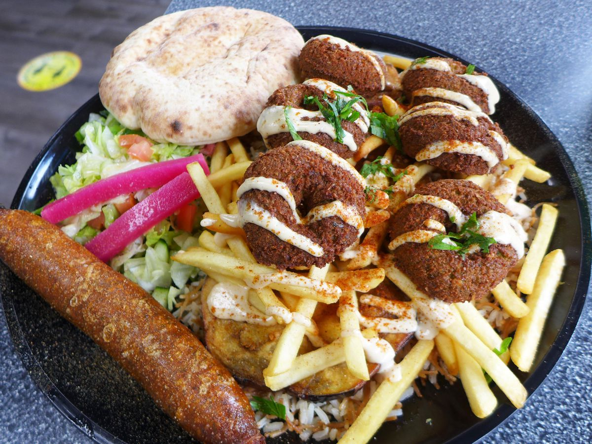 A platter with falafel squiggled with tahini, with a brown sausage on the side and salad underneath.