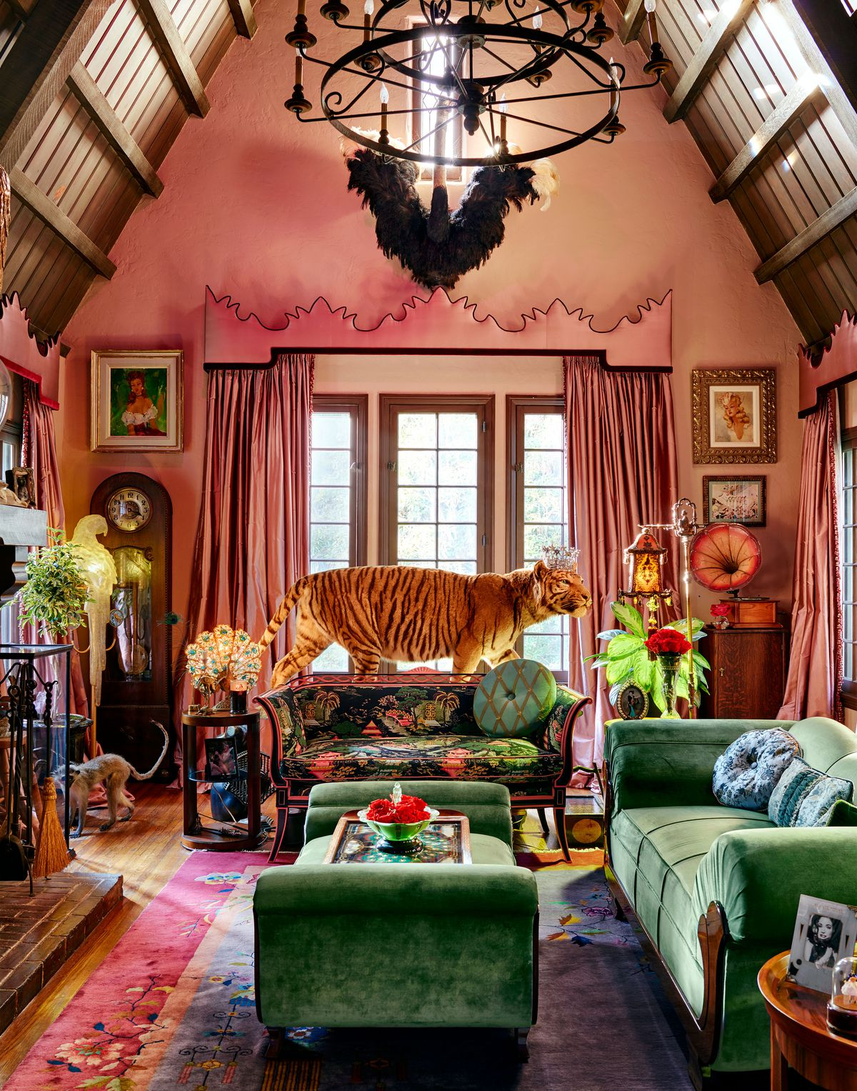 A pink room with many vintage objects in it, including taxidermy of a tiger and a monkey. A lage area rug covers the floor and there is a large ottoman and sofa, both green velvet and in the Art Deco style.