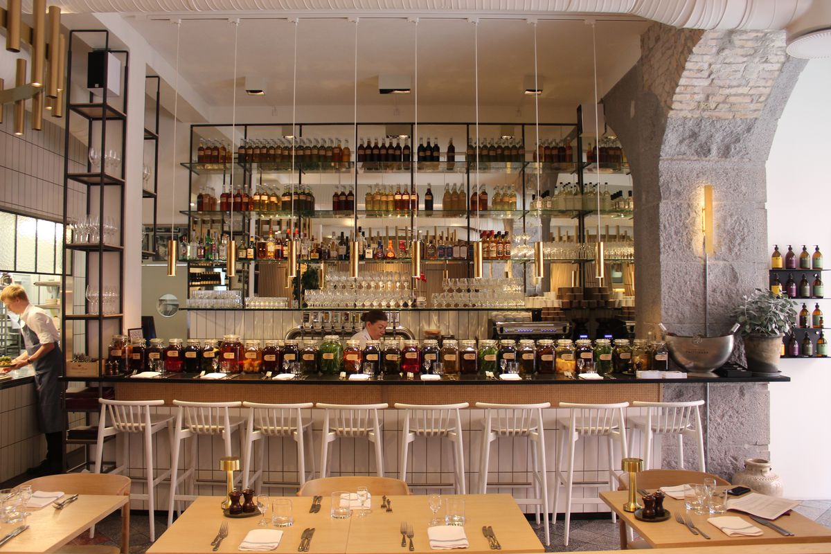 A restaurant interior with several set tables in the foreground and a bar in the background set with bar stools, decorated with pendant lights and moody dark accents all set in an exposed brick and concrete nook inside a larger, bright white space.