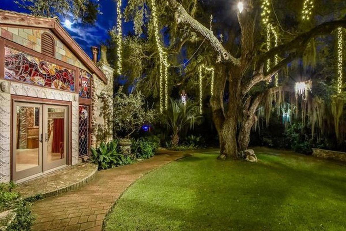 Faux-castle-style home opening to a yard with willow tree