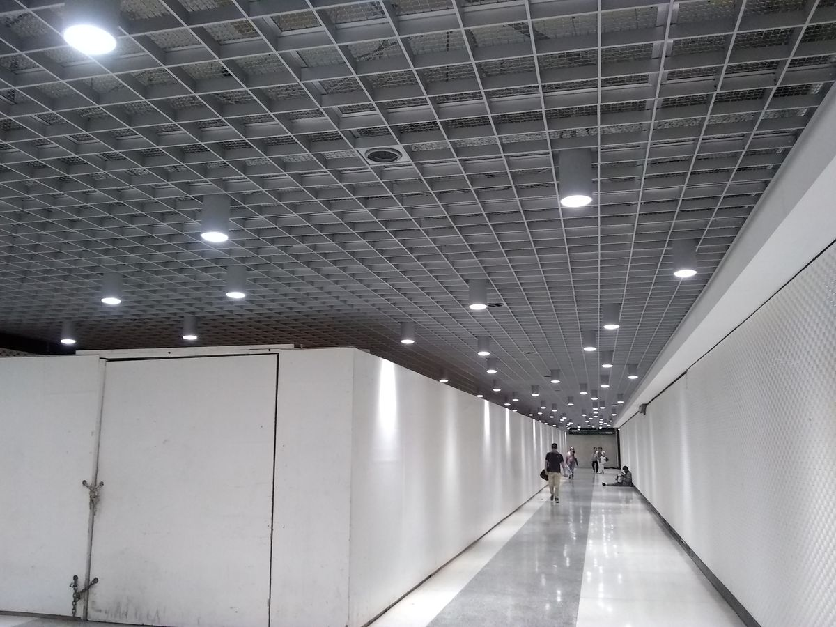 A long white corridor in an underground station, with a new, gray metal grid ceiling studded with lights.