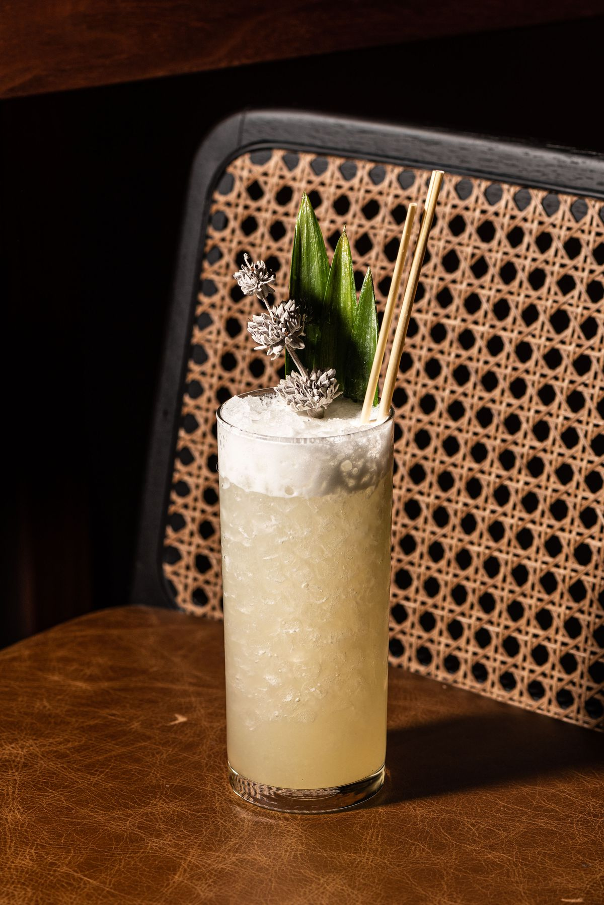 A tiki-style cocktail drink in a tall glass with a wicker chair beyond.