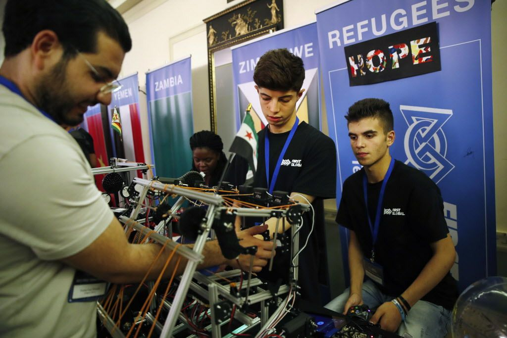 Amar Naser Kabour (center) and Mohammad Mahir Ghssan Alisawaui (right), Syrian refugees living in Lebanon, get help with their robot by their mentor, Osama Shadeh, who is also a Syrian refugee, during the FIRST Global Robotics Challenge.   Jacquelyn Marti
