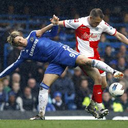 Chelsea's Fernando Torres, left, vies for the ball with QPR's Clint Hill during the English Premier League soccer match between Chelsea and Queens Park Rangers at Stamford Bridge Stadium in London, Sunday, April 29, 2012.