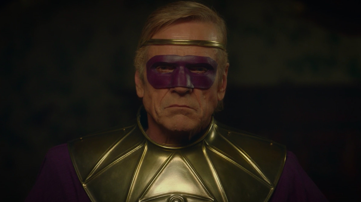 close up on veidt wearing his purple mask and looking way too old to be in costume
