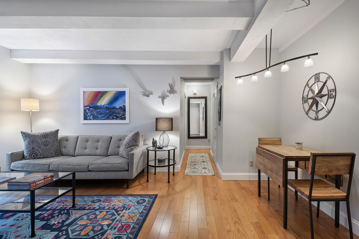 A living area with hardwood floors, light grey walls, beamed ceilings, a grey couch, and a colorful rug.