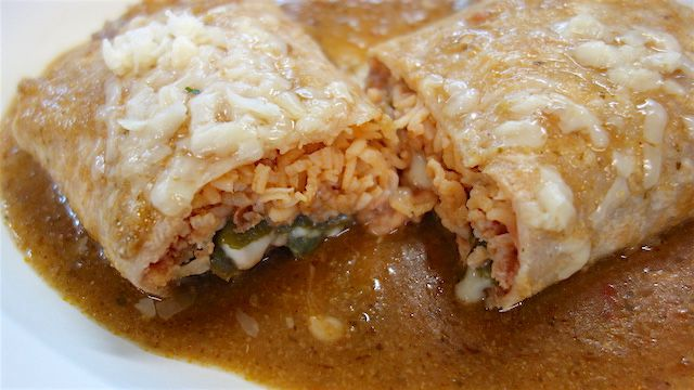 Burrito stuffed with rice, beans, and a chile rellno