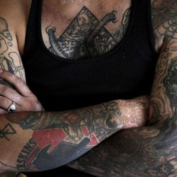 """In this Monday, Aug. 1, 2011 photo, former skinhead Bryon Widner folds his arms while resting at his home. For 16 years, Widner was a glowering, strutting, menacing vessel of hate - an """"enforcer"""" for some of America's most notorious skinhead groups. Hellbent on destruction, he had symbols of racist violence tattooed on his face. Though his beliefs had changed, leaving the old life would not be easy when it was all he had known - and when his face remained a billboard of hate."""