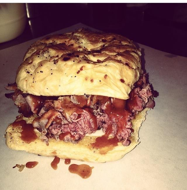 A roast beef sandwich, piled high with thinly sliced beef