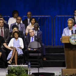 Mayor Lori Lightfoot's wife, Amy Eshleman, their daughter Vivian, former Mayor Richard M. Daley and several alderman listen as Lightfoot makes her inaugural address at Wintrust Arena, Monday morning, May 20, 2019.
