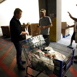 Mike Capener, left, donates a few canned goods after shopping at Walmart in Salt Lake City on Saturday, Sept. 29, 2012.  Hunger Action Month in Utah culminated with this statewide food drive to help stock the shelves of the Utah Food Bank.