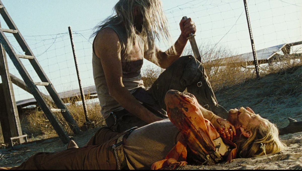 A lean, blood-covered, knife-wielding figure from The Devil's Rejects kneels next to a bloodied victim in the sand.