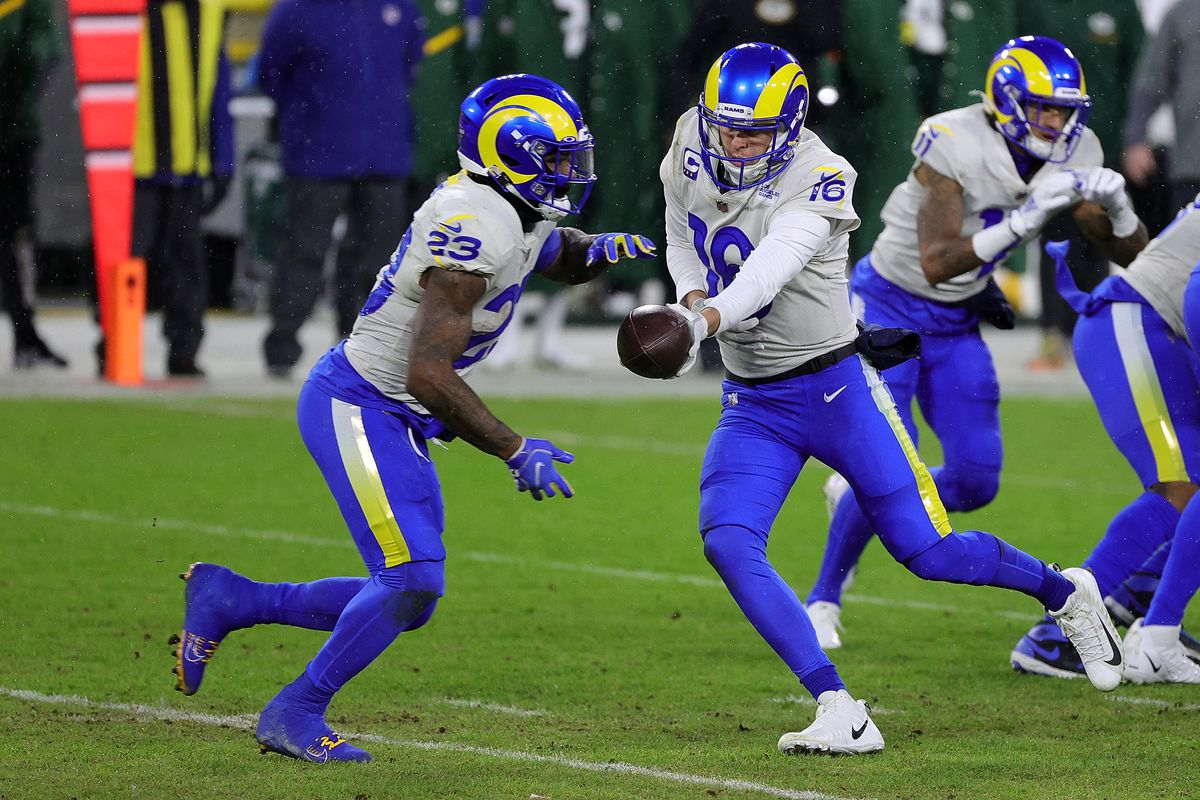 Jared Goff #16 of the Los Angeles Rams hands the ball to Cam Akers #23 during the NFC Divisional Playoff game against the Green Bay Packers at Lambeau Field on January 16, 2021 in Green Bay, Wisconsin. The Packers defeated the Rams 32-18.