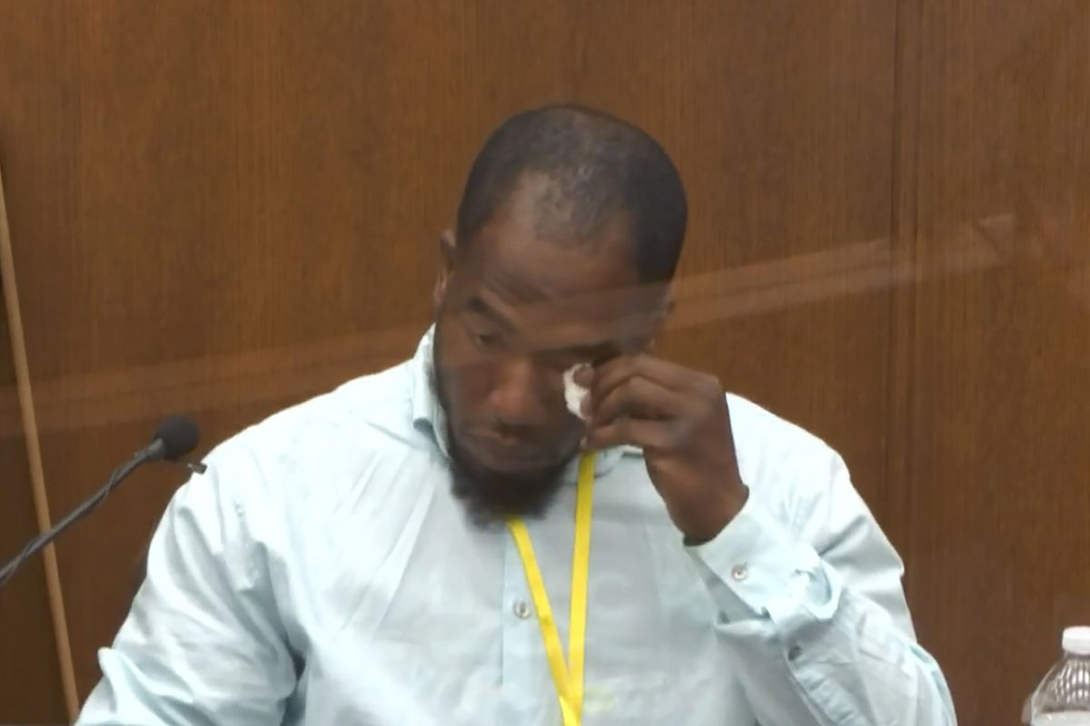 Williams, a Black man with a black goatee, dabs his eye with a tissue with a bowed head as he sits on the witness stand.