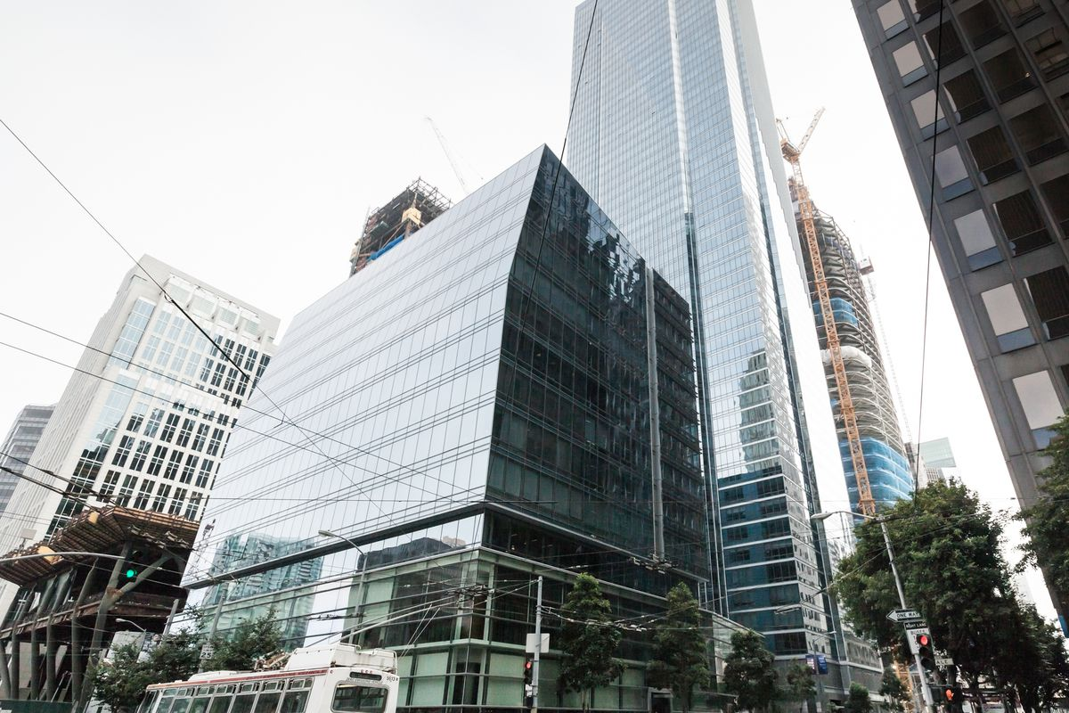 A glass-encased, 58-level tower, with a smaller podium building in the foreground.