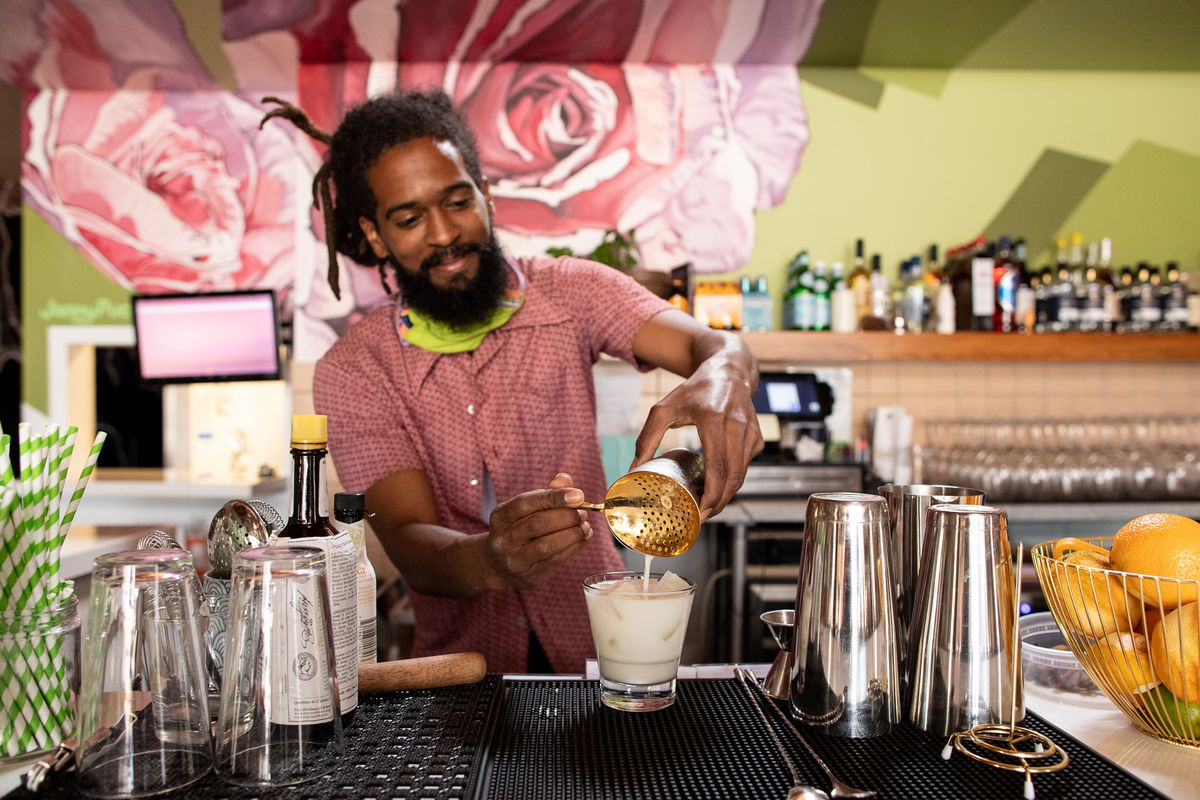 A man with a pink button up shirt, a beard, and dreadlocks tied into a bun smiles with lips closed as he stands behind a bar straining a milky white cocktail into a clear glass with ice cubes.