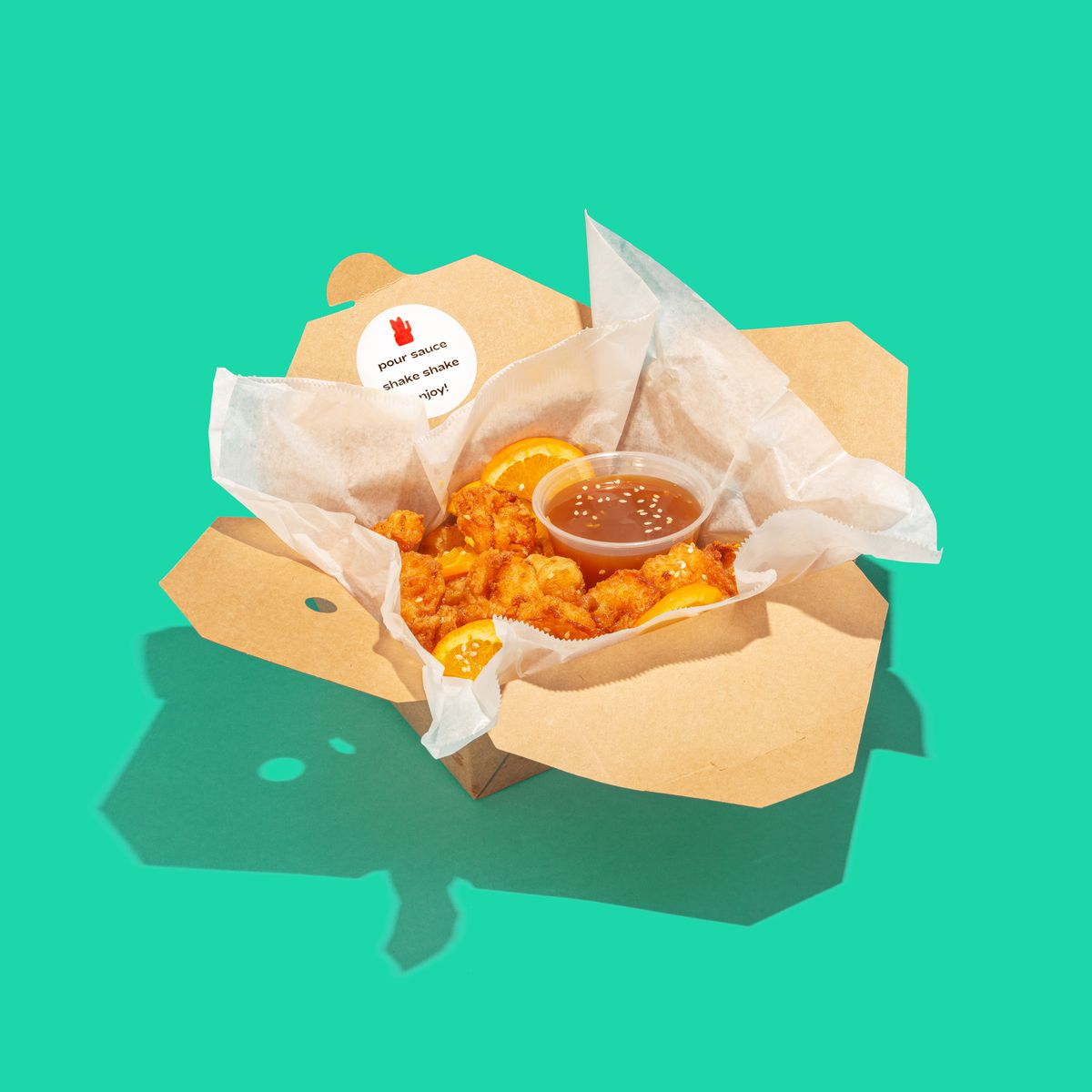 A brown box with some parchment paper inside and pieces of orange shrimp inside it