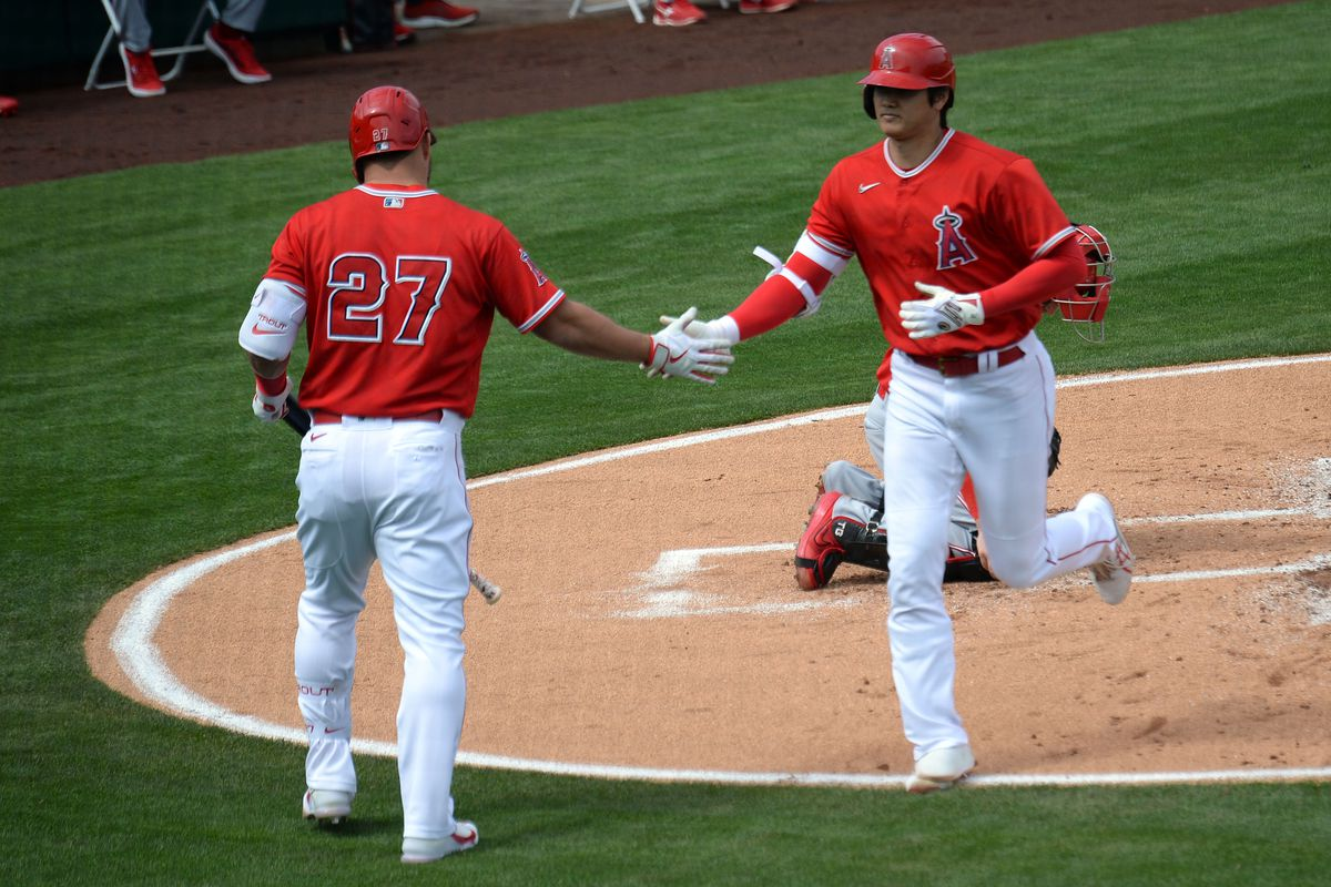 Los Angeles Angels designated hitter Shohei Ohtani (17) slaps hands with Los Angeles Angels center fielder Mike Trout (27) after hitting a home run against the Cincinnati Reds during the first inning at Tempe Diablo Stadium.