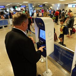 Rex Falkenrath verifies his identity by scanning his fingerprints with CLEAR, a new biometric, fee-based service that allows travelers to move past manual ID verification lines using fingerprints and iris scans, at the Salt Lake City International Airport in Salt Lake City on Wednesday, July 12, 2017.