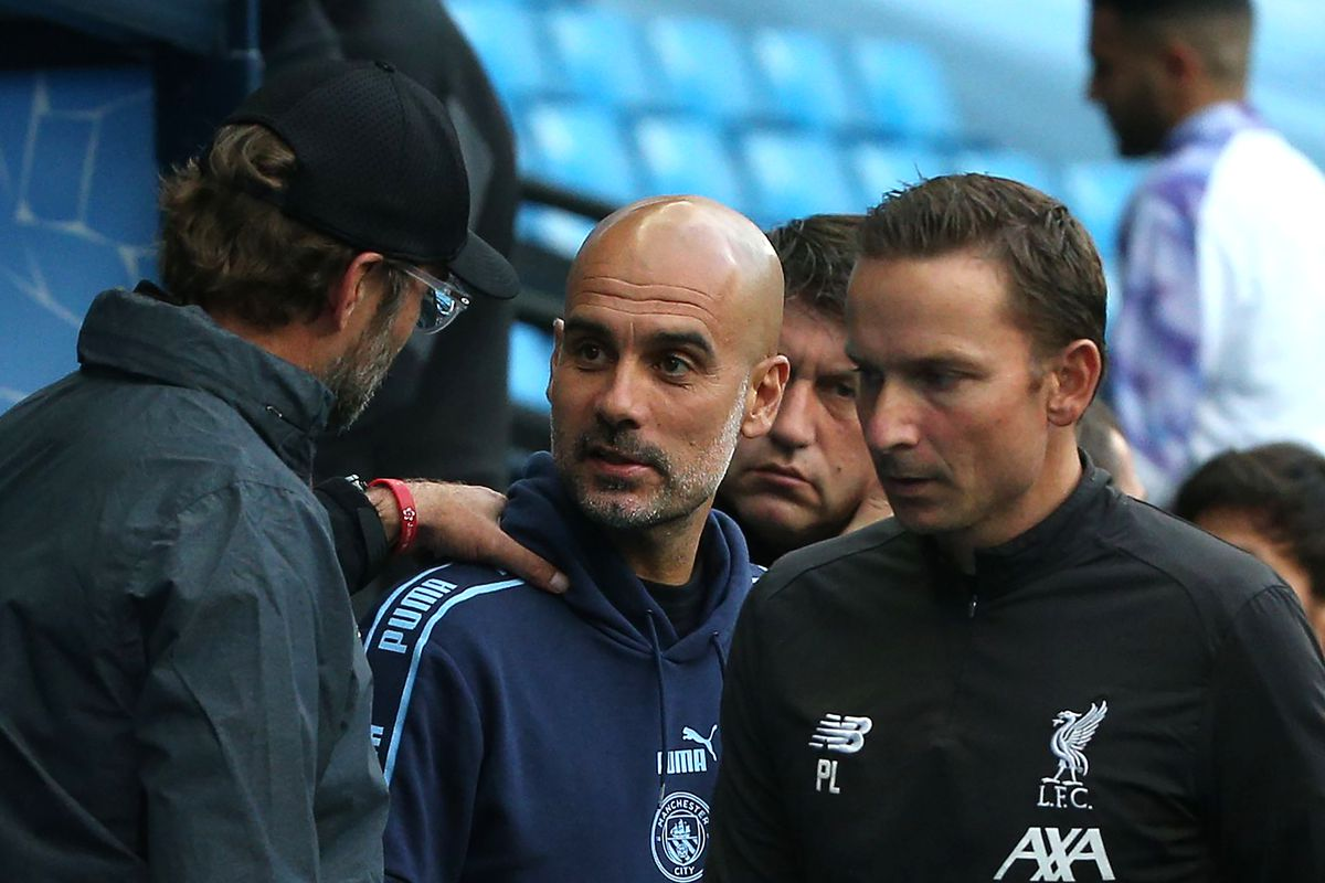 Jurgen Klopp, Manager of Liverpool speaks to Pep Guardiola, Manager of Manchester City prior to the Premier League match between Manchester City and Liverpool FC at Etihad Stadium on July 02, 2020 in Manchester, England.
