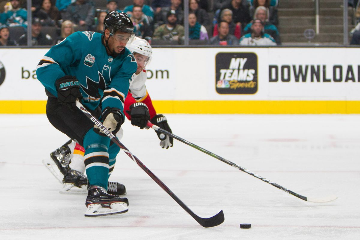 Nov 11, 2018; San Jose, CA, USA; San Jose Sharks left wing Evander Kane (9) and Calgary Flames defenseman TJ Brodie (7) battle for the puck in the third period at SAP Center at San Jose. The Sharks won 3-1.