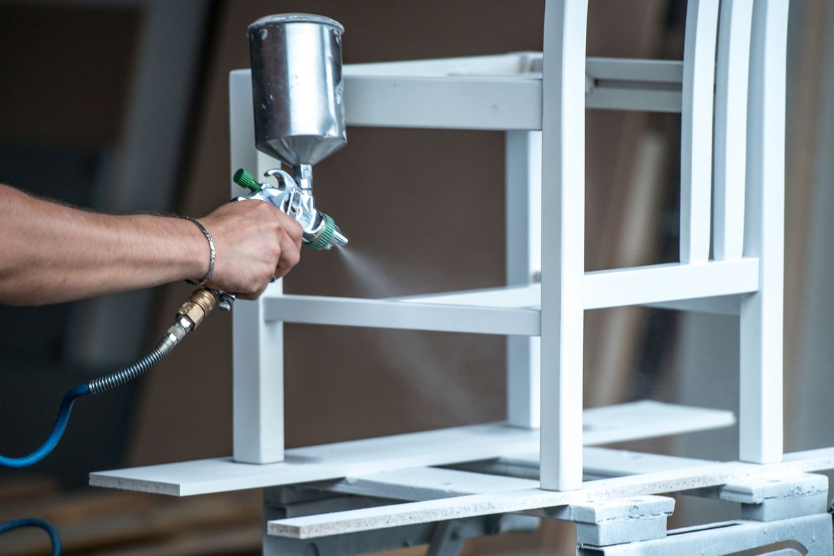 Man using professional sprayer to paint primer on wood chair.