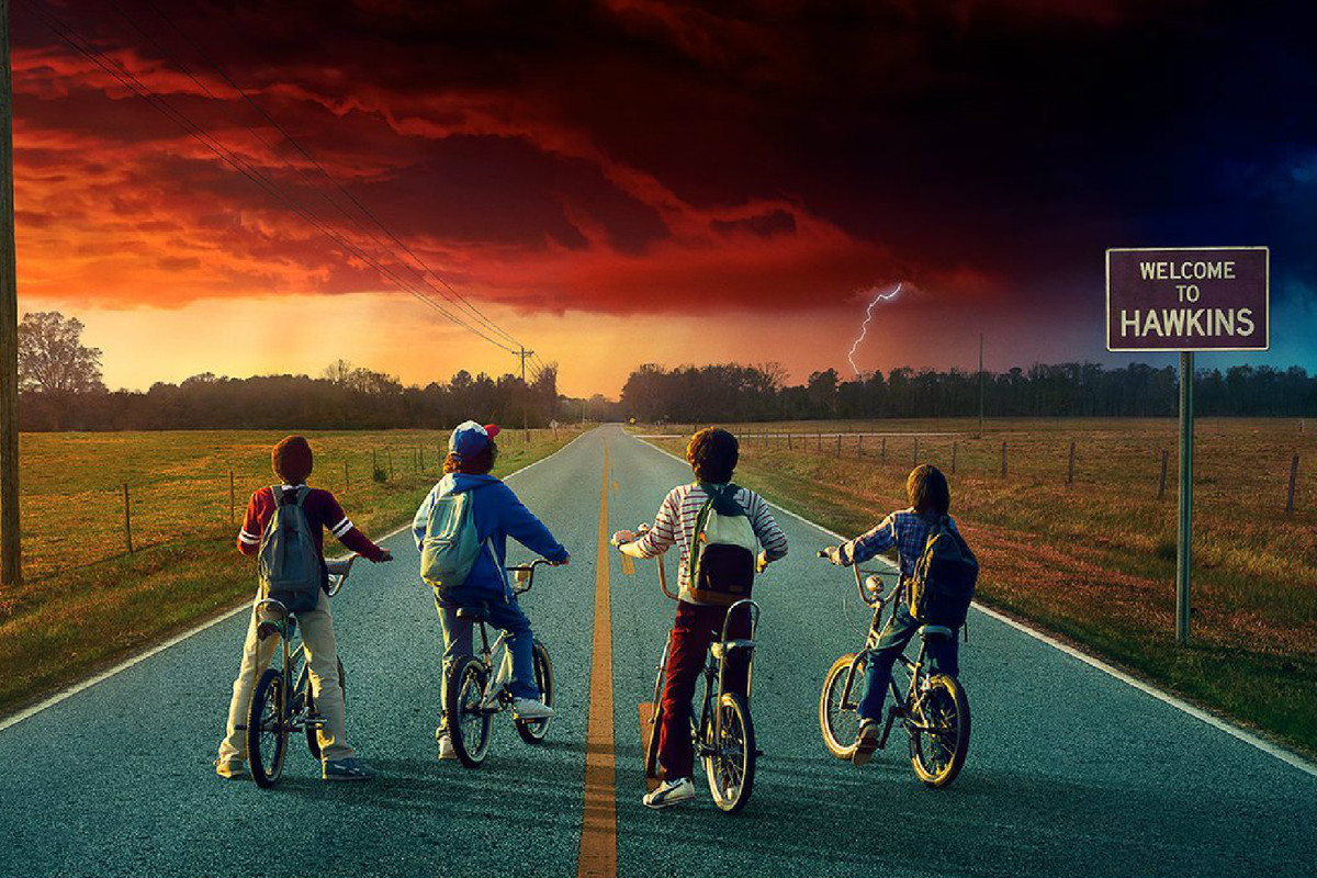"""""""Stranger Things 2"""" promo image of four kids on bikes, stopped on a paved road, looking at a threatening cloud on the horizon."""