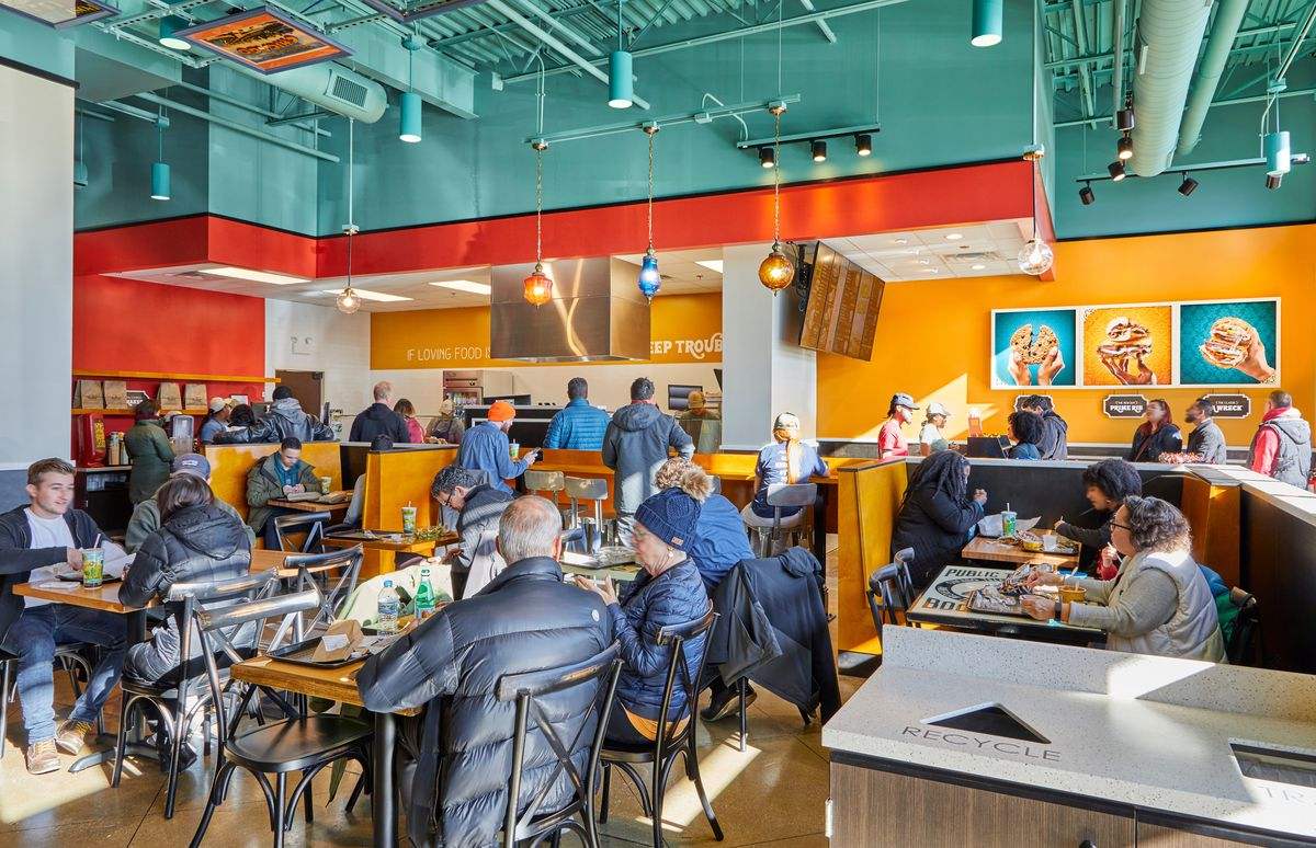 Several diners sitting at a fast-casual restaurant.
