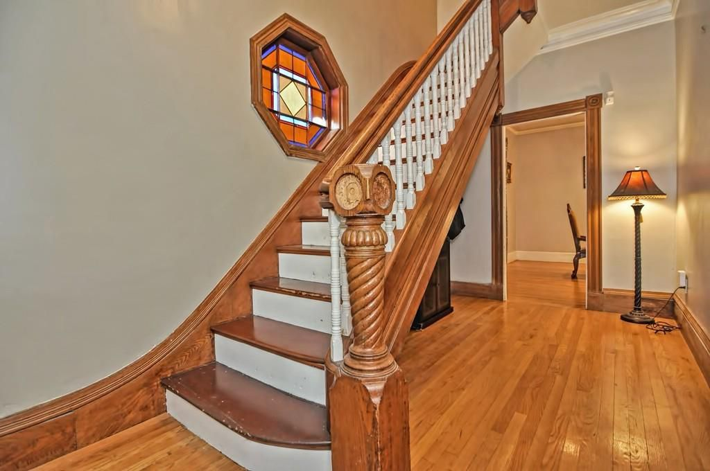 An entry foyer with a long, elegant staircase with a stained-glass window halfway up.
