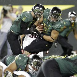 Oregon tight end Colt Lyerla, right, and quarterback Bryan Bennett both carry the football over the end zone for a touchdown during the second half of their NCAA college football game against Arizona in Eugene, Ore., Saturday, Sept. 22, 2012.   Lyerla was credited with the touchdown for breaking the plane first as Oregon won 49-0.(AP Photo/Don Ryan)
