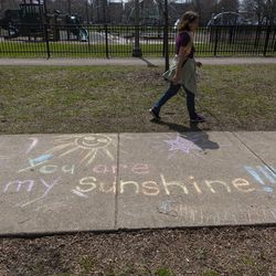 """A woman walks by sidewalk art that reads """"You are my sunshine!!!"""" at Welles Park, in the 2300 block of West Sunnyside Avenue in the Lincoln Square neighborhood."""
