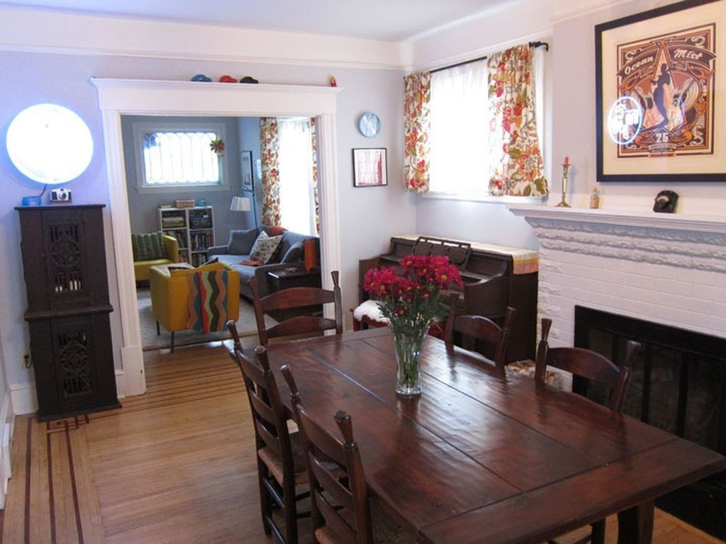 An open passageway connects a dining room with a fireplace and a living area.