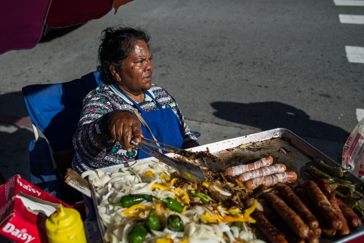 Elizabeth Bojortes prepares hot dogs at her street vending stand on a sidewalk off N Main St near Olvera St in Downtown Los Angeles.