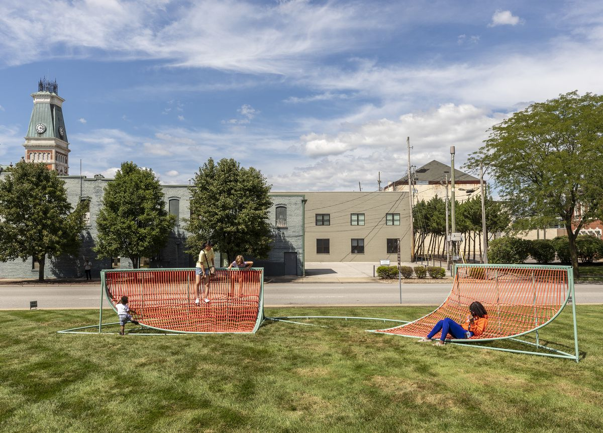 Children play on an installation of sculpture for sitting and playing that have a bright blue frame with orange woven netting fabric. They sit on a large green field.