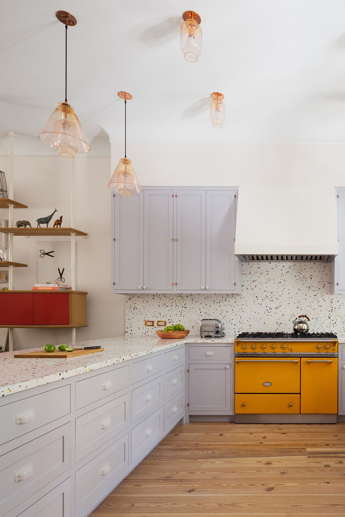 A kitchen with natural wood floors, lavender cabinets, a yellow range, and terrazzo countertops and backsplash.