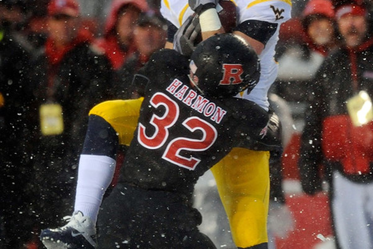 Tyler Urban of the West Virginia Mountaineers is stopped in his tracks by Duron Harmon (32) of the Rutgers Scarlet Knights.