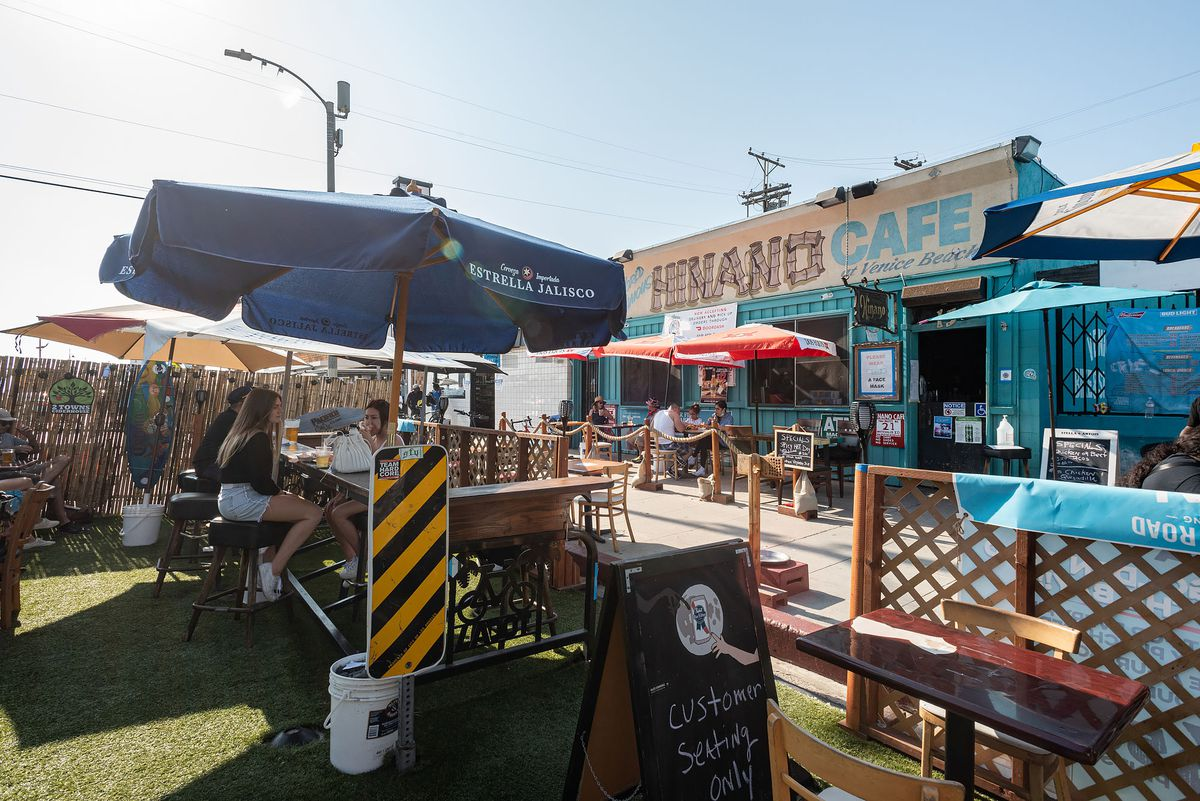 A grassy outside patio looks towards a famous Venice dive bar named Hinano Cafe.