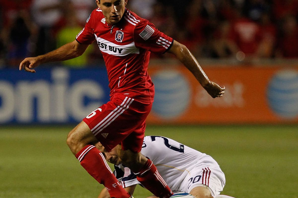 Marco Pappa #16 of the Chicago Fire moves the ball around a fallen Ned Grabavoy #20 of Real Salt Lake in an MLS match.