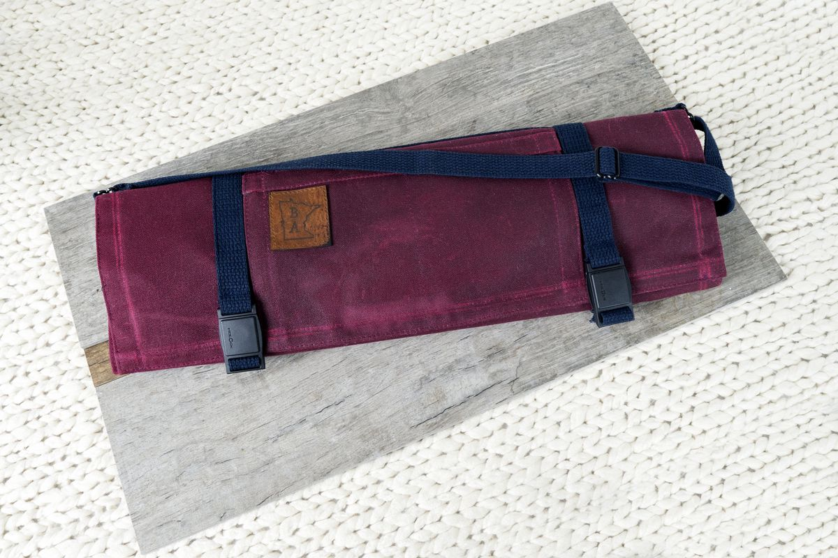A magenta colored knife roll with navy straps and details