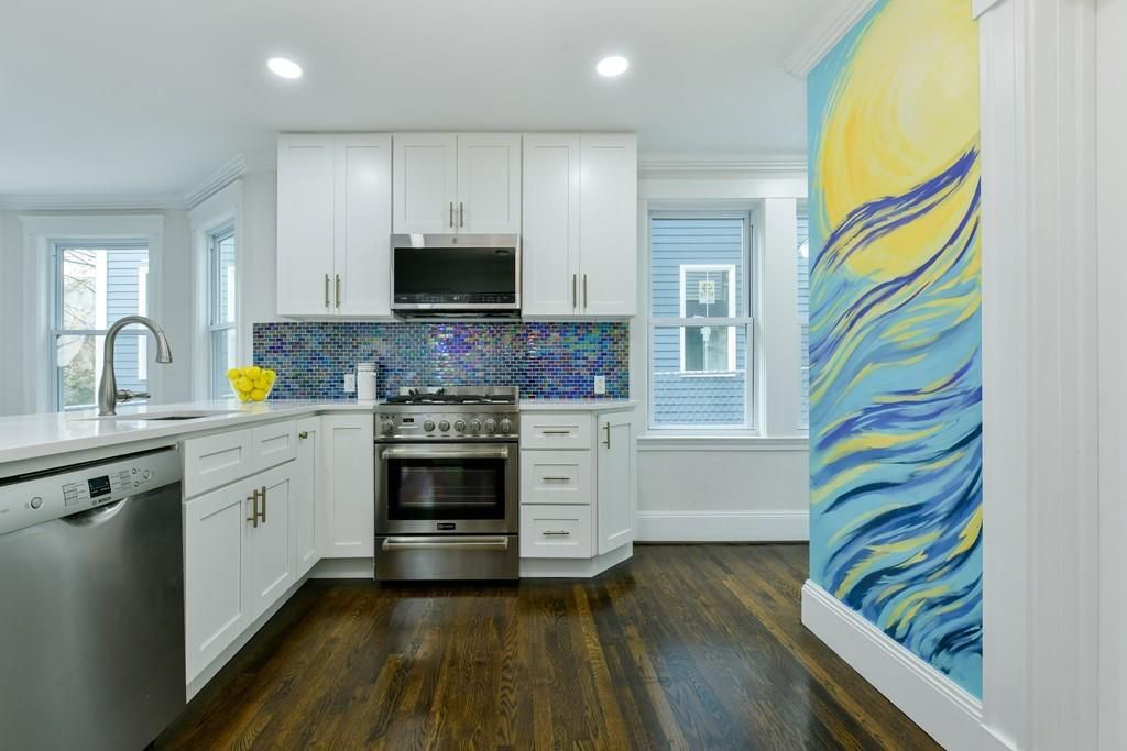 A kitchen with a long counter and a stylishly bright painted wall.