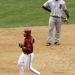 Arizona Diamondbacks' Ryan Roberts, left, rounds the bases after hitting a home run as San Francisco Giants' Pablo Sandoval looks on during the sixth inning in an MLB baseball game Sunday, April 8, 2012, in Phoenix.