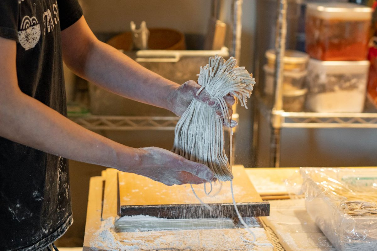 Hands shake excess flour from a bunch of soba.