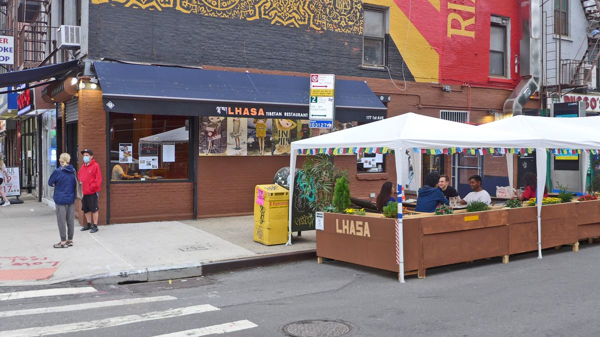 A corner storefront with part of an orange mural visible above, and outdoor tables at the curb to the right.
