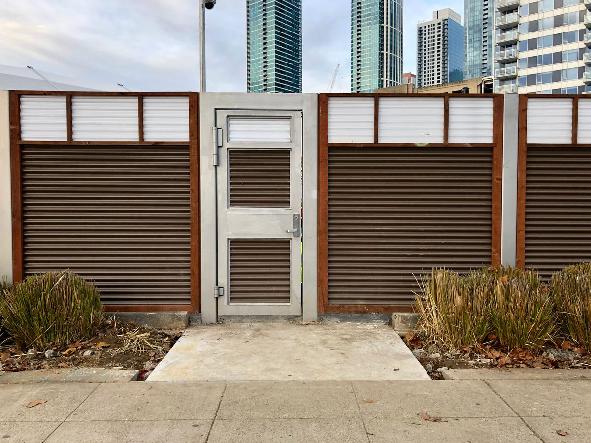 Brown corrugated steel makes up a wall with a steel door.
