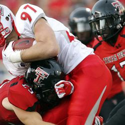 FILE - In this Sept. 15, 2012, file photo, New Mexico's Lucas Reed is tackled by Texas Tech's Blake Dees (25) and Sam Eguavoen (13) during their NCAA college football game in Lubbock, Texas. Texas Tech has long been known for slinging passes all over the Big 12.  No longer, at least through Texas Tech's first three games against non-conference opponents. The Red Raiders (3-0) are No. 2 in the nation in total defense (120 yards per game) and in passing defense (85 ypg).