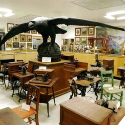 Carver Ralph Ramsey's original wood raptor from Eagle Gate, the entry to Brigham Young's farm and orchards, now hovers above desks, sewing machines and other artifacts in the DUP's Pioneer Memorial Museum. A modern Eagle Gate bridges State Street at South Temple in Salt Lake City.