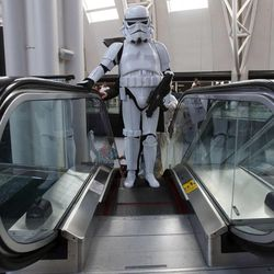 Aaron Mead, dressed as a stormtrooper from Star Wars, rides the escalator at Utah's first Comic Con at the Salt Palace Convention Center in Salt Lake City on Thursday, Sept. 5, 2013.