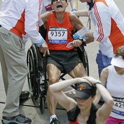 John Ouweleen, 71, of Sebastian, Fla., is helped by medical workers as he cramped up after finishing the 116th Boston Marathon in Boston, Monday, April 16, 2012. It was the second-slowest Boston race since 1985, as temperatures rising into the 80s slowed the leaders and may have convinced as many as 4,300 entrants to sit this one out.